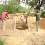 Two men raise dirt from                                                                                                           the well.